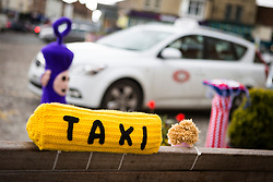 © Licensed to London News Pictures. 27/04/2016. Thirsk UK. Picture shows  a knitted taxi rank sign on a bench in Thirsk that has been Yarn Bombed. Under the cover of Darkness 300 Yarn bombing street artist's have covered the Town centre of Thirsk, the group has covered bollards, flower pots, the bus stop, tree's, benches, even the local police station. The knitted creations took over 750 balls of wool & have been placed along the route of the Tour De Yorkshire which will pass through the town during it's final stage from Middlesborough to Scarborough on Sunday.  Photo credit: Andrew McCaren/LNP
