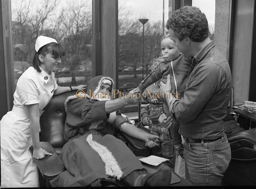 Santa Claus at Pelican House..1986..15.12.1986..12.15.1986..15th December 1986..Santa took time out from his busy and hectic schedule to donate blood at Pelican House Dublin. Christmas is a very busy time at Irelands' hospitals and a supply of blood is imperative. If Santa could make the effort why can't you, remember your donation could save a life..While still donating, Santa is pictured still having time to speak to the children.
