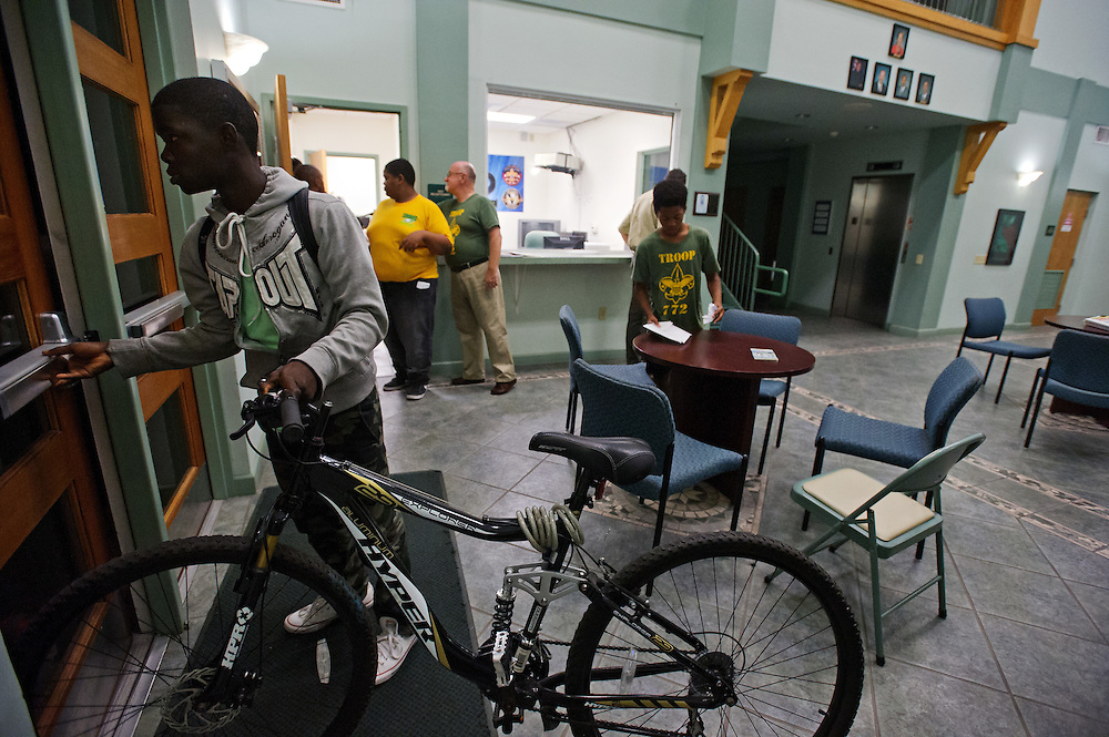 Scout Guerry Guerrier prepares to ride home on his bicycle from the Fort Pierce Police Department Willie B. Ellis Police Substation on Avenue D after a Boy Scout Troop 772 meeting on Nov. 5, 2014. Fellow scouts and volunteers gather around the office space, seen through the glass window behind him, designated for the troop's use. (XAVIER MASCAREÑAS/TREASURE COAST NEWSPAPERS)
