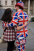 A bukser wearing a union jack suit made by Lonsdale hugs a lady tourists for souvenir picture in Trafalgar Sq.