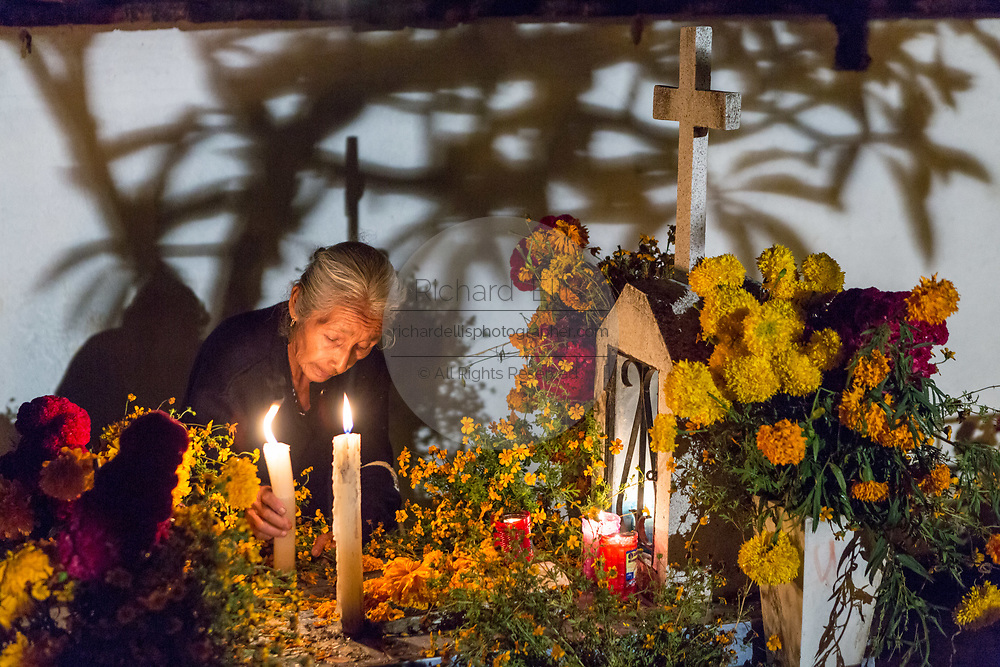 Family members light candles in honor of the dead at San Felipe de Aqua cemetery during the Day of the Dead Festival known in Spanish as Día de Muertos on November 2, 2013 in Oaxaca, Mexico.