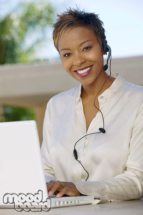 Woman on patio using laptop and headset portrait