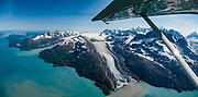 """This massive landslide across Lamplugh Glacier crashed from a 4000-foot-high mountainside collapsing in Glacier Bay National Park on June 28, 2016. The debris will eventually be carried 10 miles into Johns Hopkins Inlet. The Fairweather Range comprises the southernmost of the Saint Elias Mountains. Flightseeing from Skagway or Haines is a spectacular way to see Glacier Bay National Park, in Alaska, USA. We were bedazzled by Mountain Flying Service's 1.3-hour West Arm tour from Skagway. Glacier Bay is honored by UNESCO as part of a huge Biosphere Reserve and World Heritage site shared between Canada and the United States. In 1750-80, Glacier Bay was totally covered by ice, which has since radically melted away. In 1794, Captain George Vancover found Icy Strait on the Gulf of Alaska choked with ice, and all but a 3-mile indentation of Glacier Bay was filled by a huge tongue of the Grand Pacific Glacier, 4000 feet deep and 20 miles wide. By 1879, naturalist John Muir reported that the ice had retreated 48 miles up the bay. In 1890, """"Glacier Bay"""" was named by Captain Beardslee of the U.S. Navy. Over the last 200 years, melting glaciers have exposed 65 miles of ocean. As of 2019, glaciers cover only 27% of the Park area. Since the mid 1900s, Alaska has warmed 3 degrees Fahrenheit and its winters have warmed nearly 6 degrees. Human-caused climate change induced by emissions of greenhouse gases continues to accelerate warming at an unprecedented rate. Climate change is having disproportionate effects in the Arctic, which is heating up twice as fast as the rest of Earth. This image was stitched from multiple overlapping photos."""