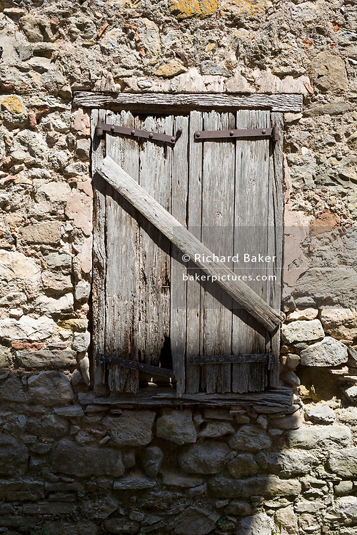 In afternoon heat, baked hard paint textures on village closed wooden shutters, on 26th May, 2017, in Villerouge-Termenes, Languedoc-Rousillon, south of France