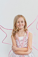 Portrait of a happy young girl with arms crossed over colored background