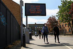 © Licensed to London News Pictures. 25/04/2020. London, UK. Members of public walk past 'STAY HOME ESSENTIAL TRAVEL ONLY SAVE LIVES' digital sign in Tottenham, north London during coronavirus lockdown. The lockdown continues to slow the spread of COVID-19 and reduce pressure on the NHS. Photo credit: Dinendra Haria/LNP