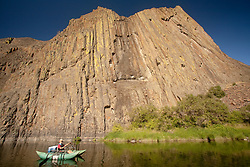 North America, United States, Oregon, John Day River, boy (age 11) rowing pontoon raft under huge columnar basalt rock formation.  MR