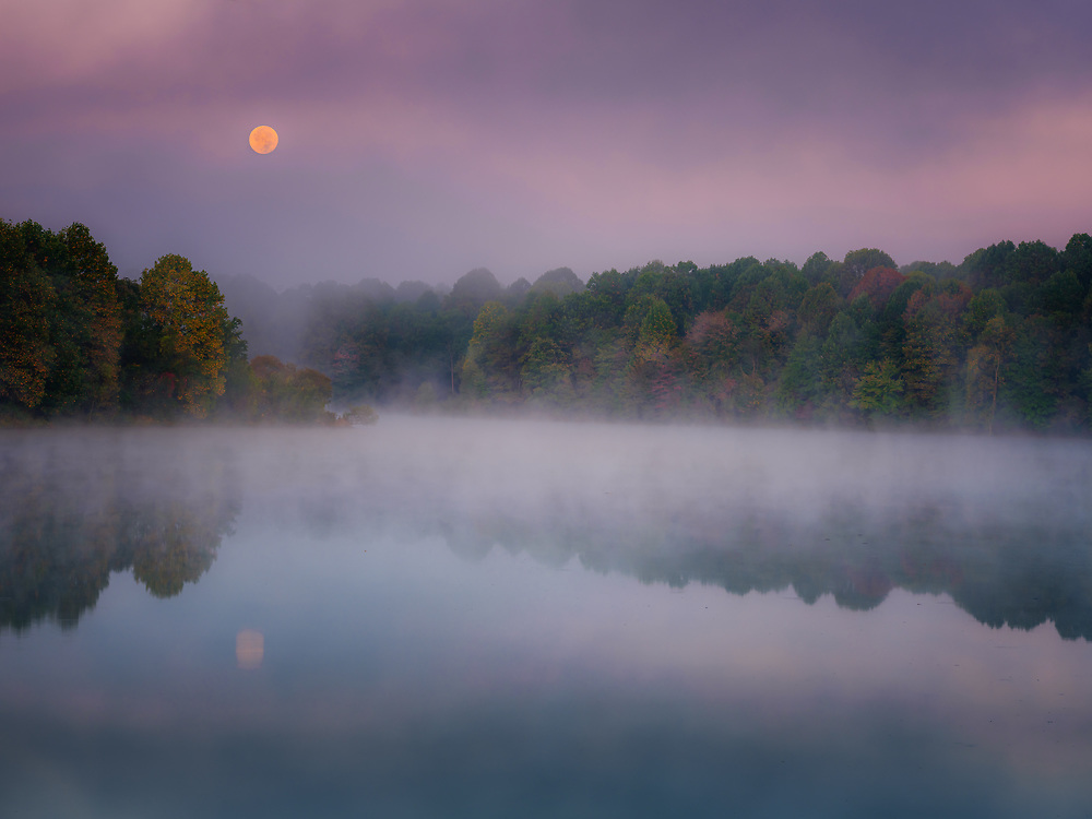 Hunter moon sets over Centennial Lake in Columbia, Maryland.