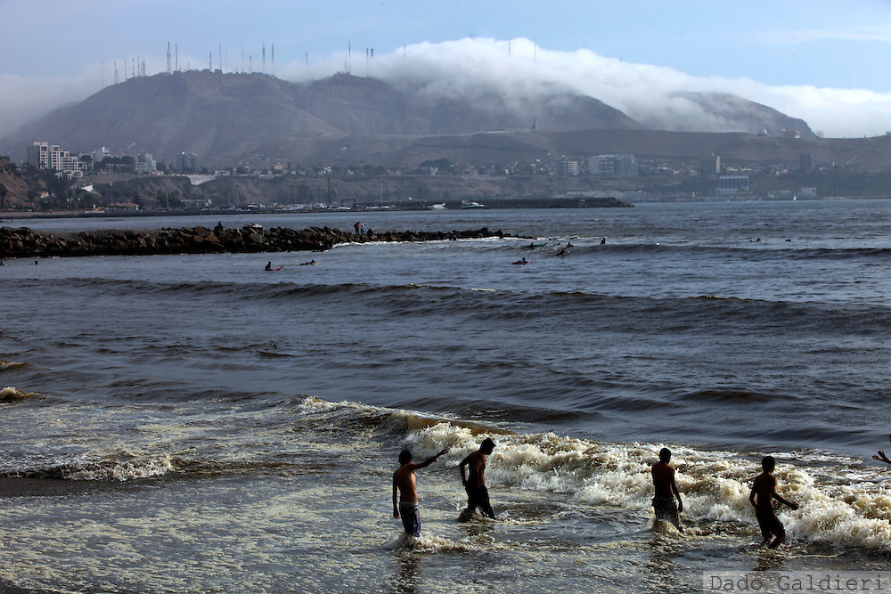 Bathers enjoy the beginning of the summer in the misty coastline of Lima, Peru, Thursday, Dec. 23, 2010.(Photo Dado Galdieri)
