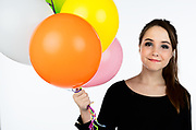 Pretty pre-teen model holding colorful party balloons.