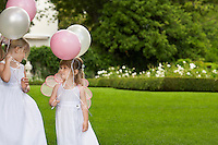 Two young girls in garden wearing white dresses holding balloons