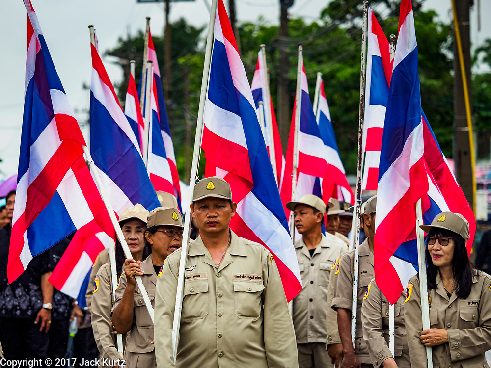 04 OCTOBER 2017 - CHONBURI, CHONBURI, THAILAND: Civil defense volunteers carry the Thai flag in the parade before the buffalo races. Contestants race water buffalo about 100 meters down a muddy straight away. The buffalo races in Chonburi first took place in 1912 for Thai King Rama VI. Now the races have evolved into a festival that marks the end of Buddhist Lent and is held on the first full moon of the 11th lunar month (either October or November). Thousands of people come to Chonburi, about 90 minutes from Bangkok, for the races and carnival midway.   PHOTO BY JACK KURTZ