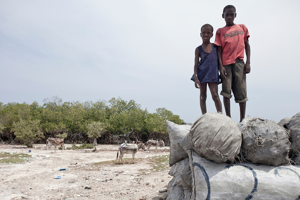 Two boys stand on bags of charcial waiting to be shipped from Ile de La Gonave, Haiti