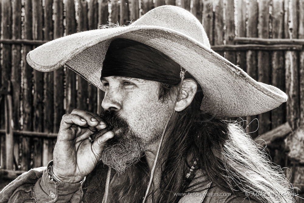 Taos style Mountain Man taking a puff on his hand rolled cigar at Historic Fort Bridger.
