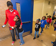 Chameka Scott gets a hug from a student during a Touchdown Houston Read On literacy program at Ross Elementary School, December 2, 2016.