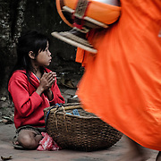 A young girl begs for food while Buddhist monks and novices in their bright saffron robes walk in single file past locals and tourists offering food in an early morning ritual known as tak bat.