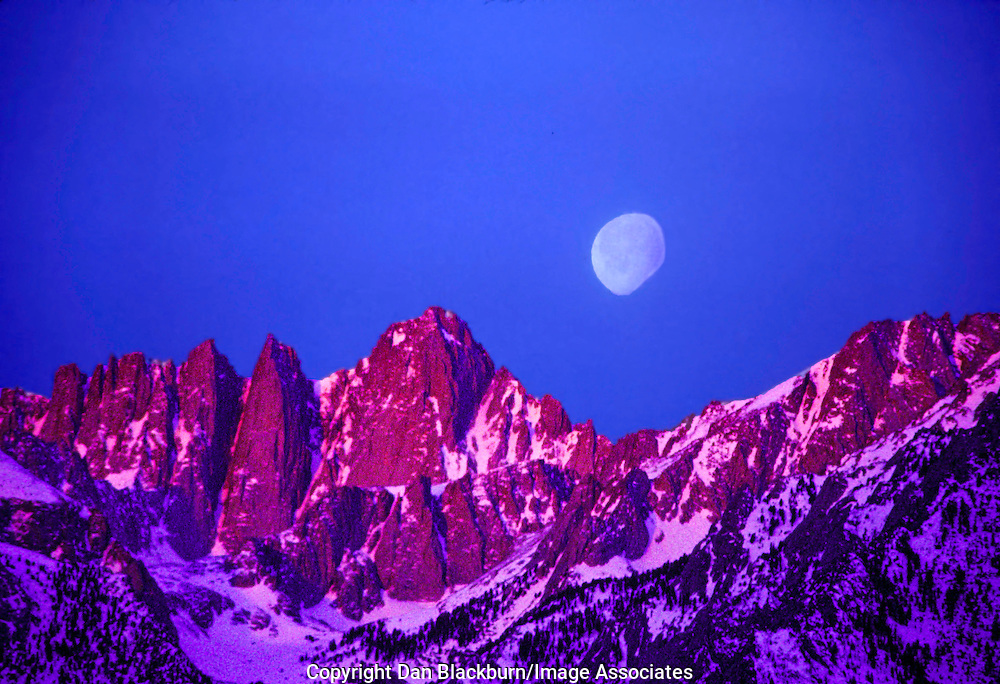 An almost full moon sets over Mt. Whitney in the Eastern Sierra of California while the rising sun lights the mountains below.