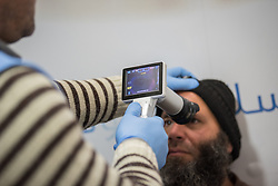 26 February 2020, Abu Dis, Palestine: 43-year-old construction worker Ziad Halabeye from Abu Dis prepares to have a fundus photo taken to check his retina, adminsitered by supervisor Ziad Paradiah, as he visits the Augusta Victoria Hospital's Mobile Diabetes Clinic. In an effort to make Diabetes services more accessible to people in the West Bank, the Augusta Victoria Hospital offers a Mobile Diabetes Clinic, which moves around to various locations in the West Bank, offering screening and routine testing for Diabietes and the symptoms it causes.