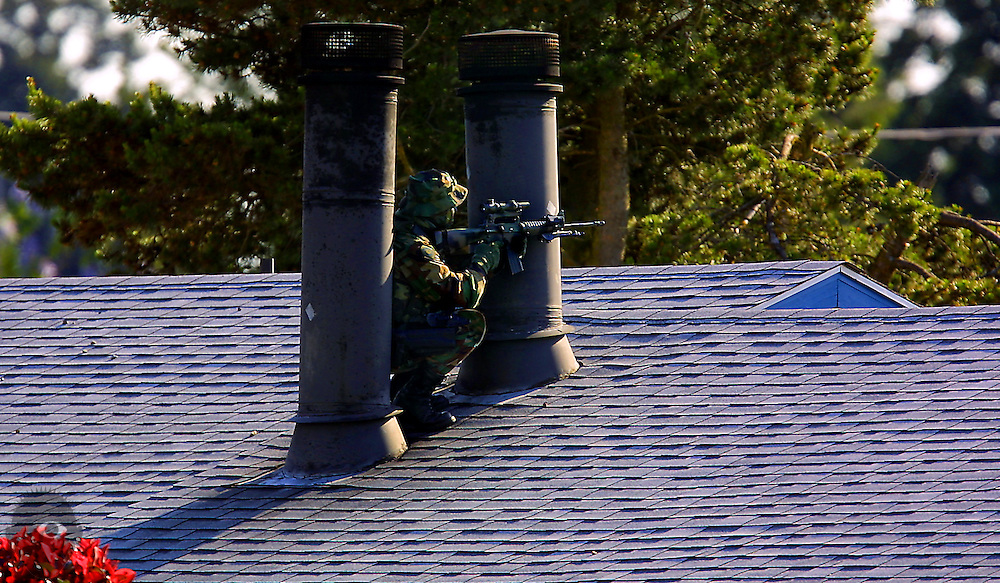 A comouflaged Special Emergency Reaction Team sniper takes a position on a Portland roof adjacent to the Fairway Apartments. They were in a standoff with Ron Studer, 34, who held his 5 children captive yet hours released them without harm.