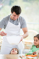 Smiling father preparing sandwich with daughters at home