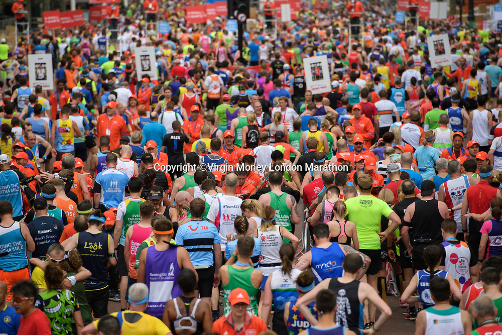 Runners having criossed the finishing line shuffle forwards to collect their medals. The Virgin Money London Marathon, 23rd April 2017.<br /> <br /> Photo: Thomas Lovelock for Virgin Money London Marathon<br /> <br /> For further information: media@londonmarathonevents.co.uk