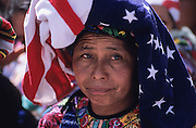 Quetzaltenango: San Juan Ostuncalco, fiesta of San Juan Bautista. Instead of traditional dress many women utilise US flags coming from Mayan relatives that migrated in United States.