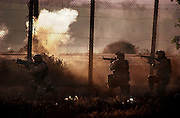 U.S. Marines from 3rd Battalion 4th Marines return fire during a gunfight with Saddam Fedayeen gunmen on the banks of the Tigris River next to the Palestine Hotel Apil 12, 2003 in Baghdad, Iraq.