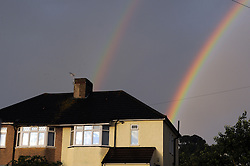 © Licensed to London News Pictures. 28/06/2014<br /> A double rainbow ends behind some Orpington homes in Kent.<br /> Heavy rain and rainbows this evening  (28.06.2014) across the South East of the UK.<br /> (Byline:Grant Falvey/LNP)