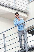 Full length portrait of young businessman having coffee at hotel balcony