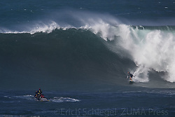 December 13, 2017 - Waimea Bay, HI, USA - WAIMEA BAY, HI - DECEMBER 13, 2017 - A surfer drops in on a large wave at Waimea Bay. The big wave surfing spot only breaks in the winter when storms send large north swells toward the North Shore of Oahu. (Credit Image: © Erich Schlegel via ZUMA Wire)