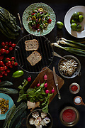 Assortment of fresh ingredients of the vegan cuisine, fresh salad of valerian, sprouts, tomatoes, radishes, spring onions, black tuscan broccoli and limes. Flat lay food background.
