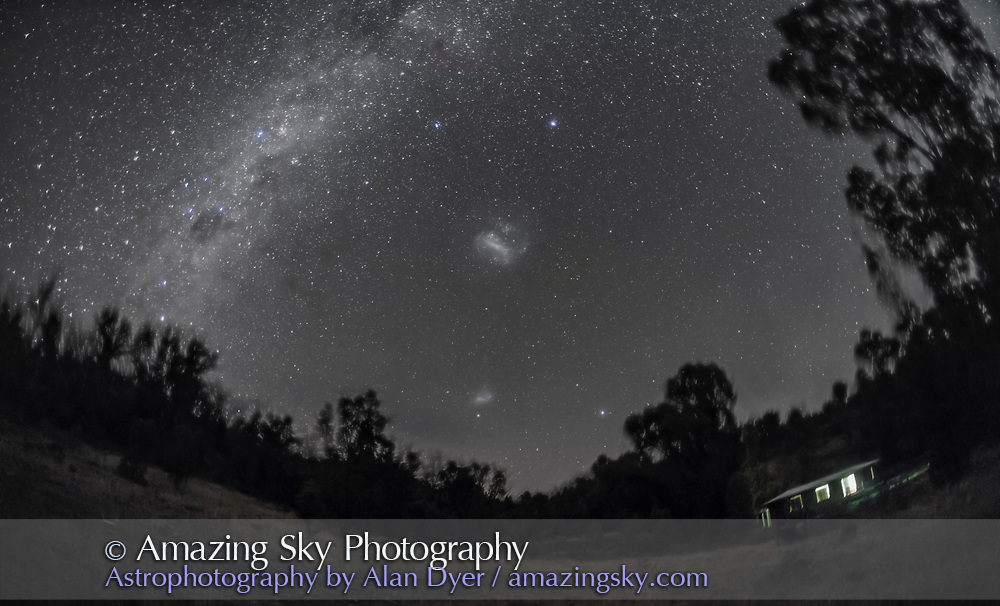 The region of sky around the South Celestial Pole, at left, and to the west at right. The two Magellanic Clouds are at centre, the Large one above and the Small Cloud below. The bright star Archernar is at top. At left is the southern Milky Way including Carina, Crux and Centaurus. The Carina Nebula is at upper left with the Southern Cross Below it and Alpha and Beta Centauri rising above the trees. The house is the Tibuc Gardens Cottage, my residence for my 2016 Australia astrophoto excursion. Yes, I left the light on!<br /> <br /> This is a stack of 5 x 1.5-minute exposures at f/2.8 with the 15mm full-frame fish-eye lens and Canon 5D MkII at ISO 3200, with the ground coming from one of the tracked exposures to minimize trailing. This version of the image has been processed to make the view better resemble what you see with the unaided eye, in a largely monochrome and softer view than the colourful and high-contrast views commonly presented in astrophotos. Even at that there is more fine structure present in the Milky Way than the unaided eye usually sees, though binoculars beging to reveal that smaller detail. I have left some colours in some stars and in the foreground of landscape scenes.