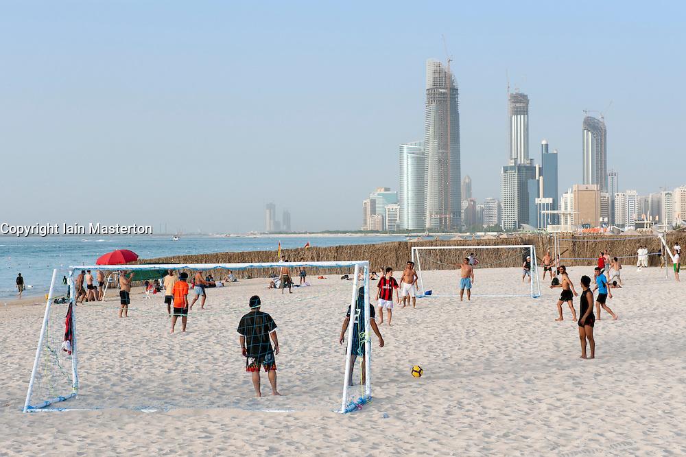 People playing football on beach in Abu Dhabi United Arab Emirates UAE