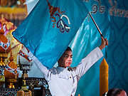 12 AUGUST 2015 - BANGKOK, THAILAND: A Thai student holds up the Queen's flag during a program to honor Queen Sirikit of Thailand on her 83rd birthday. Queen Sirikit was born Mom Rajawongse Sirikit Kitiyakara on August 12, 1932. She is the queen consort of Bhumibol Adulyadej, King (Rama IX) of Thailand. She met Bhumibol in Paris, where her father was the Thai ambassador. They married in 1950, she was appointed Queen Regent in 1956. The King and Queen had one son and three daughters. She has not made any public appearances since her hospitalization in 2012. Her birthday is celebrated as Mother's Day in Thailand, schools and temples across Thailand hold ceremonies to honor the Queen and mothers.    PHOTO BY JACK KURTZ