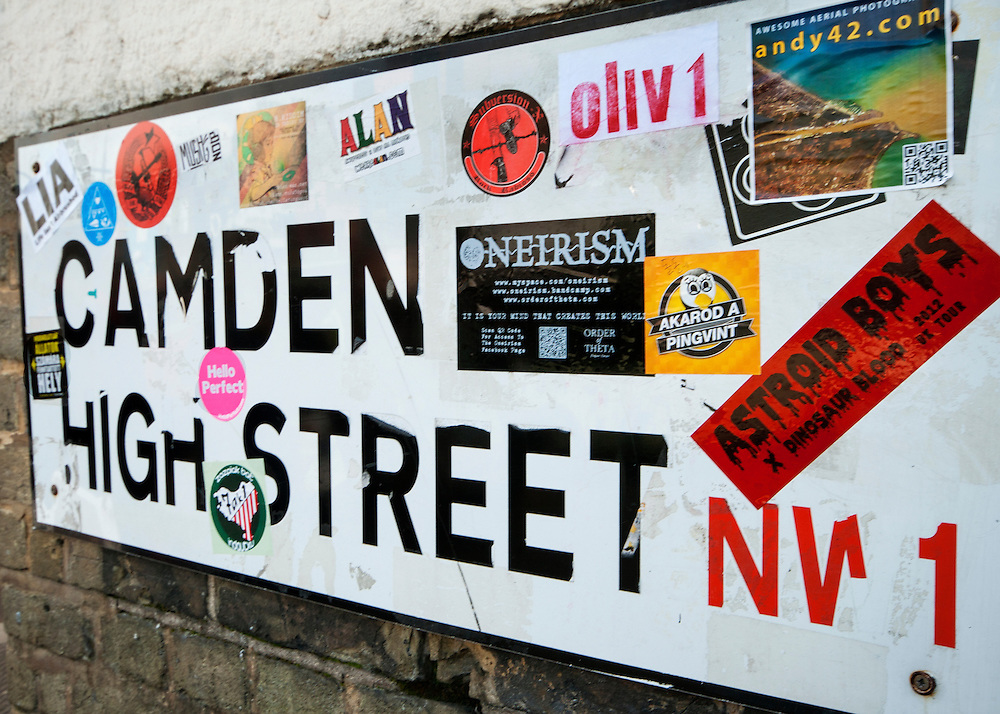 A street sign covered in stickers. Camden High Street is a popular tourist destination in North London.