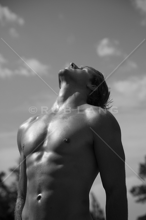 man without a shirt leaning back to soak up the sun