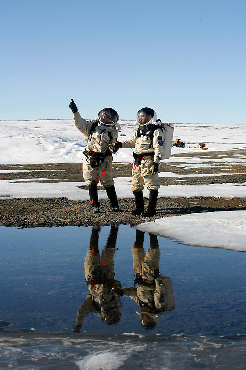 Kathryn Bywaters -27  Ryan Kobrick -27 (on the left) walking next to  Lake Trinity and collect samples for there research abut the ice cap  on  planet Mars ..Devon island Wednesday June, 6, 2007...Mars flashline Mars arctic (FMARS)..On Devon Island in the high Canadian Arctic a group of sciences from the USA & Canada is gathering for four month to search watt human being can do on mars planet..The four month mission will be the first time that a simulated Mars mission has ever been conducted for such a long duration..The crow of volunteers includes some biologist geologist and other nether scientist researches...They chose Devon Island in Canada because it simulated the acclaim on the planet Mars, for getting the filling of being on Mars and to challenge the research and to make it close as they can to the conditions on the planet they wear spies suit and live isolated in the laboratory for four month..The man person that ran the project is Dr Robert Zabrin that believe that this project can lied to find ways to search for life on Mars and maybe to fined a way that human being will be able to live on the planet...This project is privet projects that cooperate with several universities around the world...