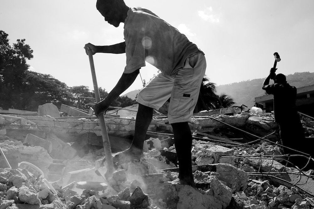 Two men dig through the rubble of a collapsed building that was destroyed in the recent earthquake to salvage metal in Port-au-Prince, Haiti.