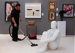 © licensed to London News Pictures. LONDON, UK  08/06/2011. An exhibitor hoovers around a self portrait sculpture by Jaume Plensa for sale at the Olympia International Fine Art & Antiques Fair. All 30,000 items on sale from 150 dealers are vetted for authenticity by a panel of experts. The show opens in Olympia tomorrow (Thursday) and runs for 11 days. Please see special instructions for usage rates. Photo credit should read CLIFF HIDE/LNP