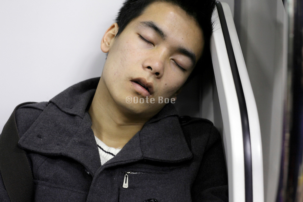 portrait of young adult Asian man during a commuting nap