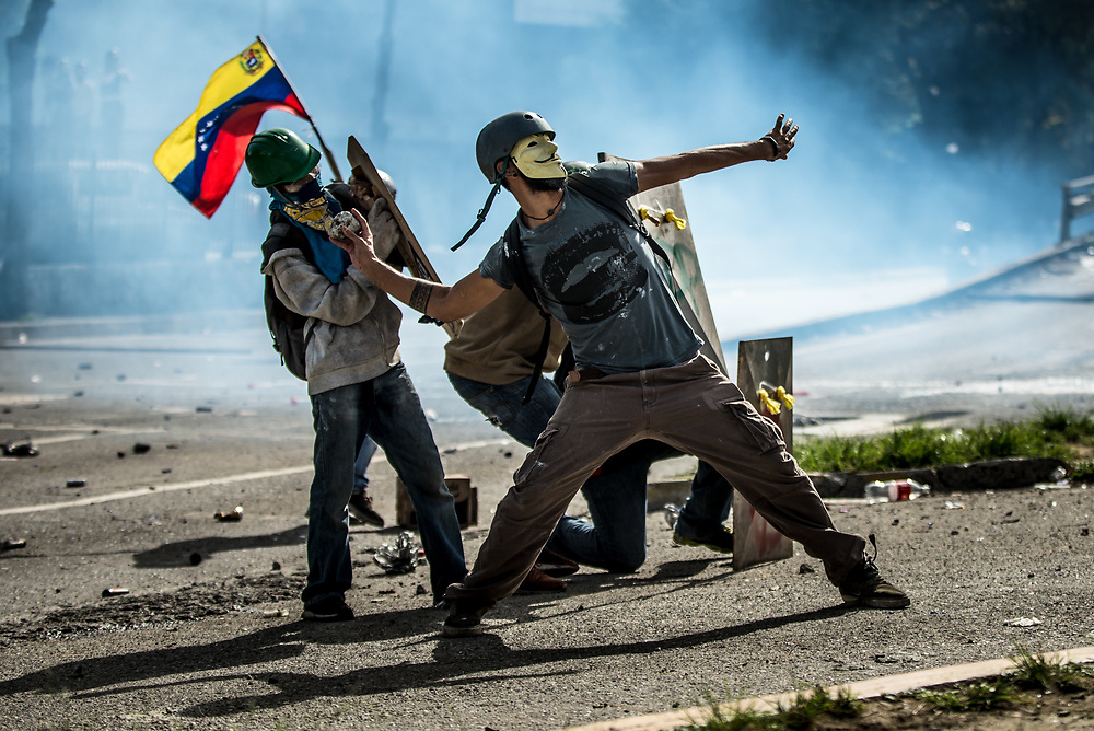 CARACAS, VENEZUELA - MAY 24, 2017:  Anti-government protesters use homemade shields and throw rocks and molotov cocktails at National Guard soldiers, who responded by heavily tear gassing and firing rubber bullets and buckshot at them.  The streets of Caracas and other cities across Venezuela have been filled with tens of thousands of demonstrators for nearly 100 days of massive protests, held since April 1st. Protesters are enraged at the government for becoming an increasingly repressive, authoritarian regime that has delayed elections, used armed government loyalist to threaten dissidents, called for the Constitution to be re-written to favor them, jailed and tortured protesters and members of the political opposition, and whose corruption and failed economic policy has caused the current economic crisis that has led to widespread food and medicine shortages across the country.  Independent local media report nearly 100 people have been killed during protests and protest-related riots and looting.  The government currently only officially reports 75 deaths.  Over 2,000 people have been injured, and over 3,000 protesters have been detained by authorities.  PHOTO: Meridith Kohut