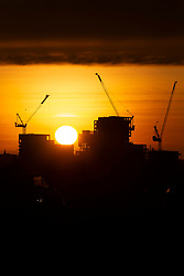 © Licensed to London News Pictures. 03/12/2019. London, UK. Sunrises over a cranes during a cold and crisp on Blackheath. Temperatures will continue to drop to 2° this evening.   Photo credit: George Cracknell Wright/LNP