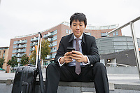 Asian businessman with luggage text messaging through cell phone against buildings