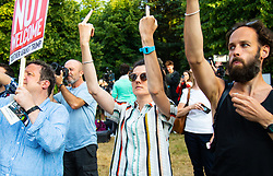A woman makes an obscene gesture as a helicopter departs as protesters create a big noise in Regent's Park, London, outside the US Ambassador's residence where President Donald Trump is staying. London, July 12 2018.