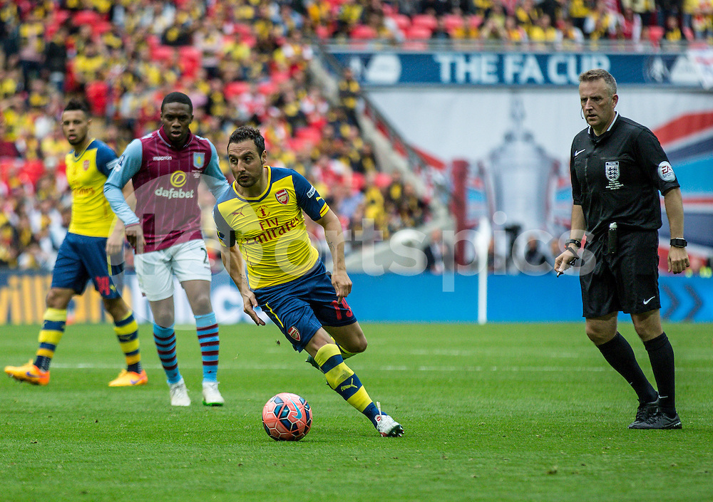 Santi Cazorla of Arsenal with the ball as referee Jonathan Moss looks on during the The FA Cup Final match between Arsenal and Aston Villa at Wembley Stadium, London, England on 30 May 2015. Photo by Liam McAvoy.