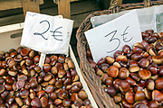 Baskets of autumnal chestnuts for sale at a fruit and veg market in Santiago de Compostela, Galicia, Spain.