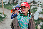 A girl holding a baby while playing at the temple complex at Chitkul Village of Kinnaur