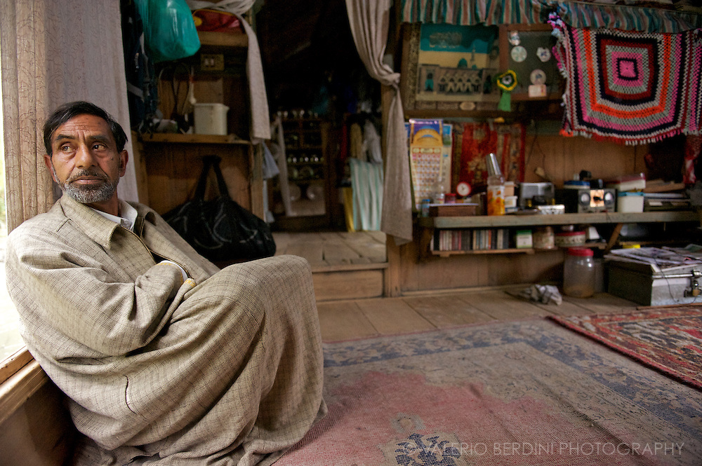Old man in a traditional woollen clothe in the living room of a more comfortable houseboat docked on the Jelhum river in Srinagar. Kashmir. India