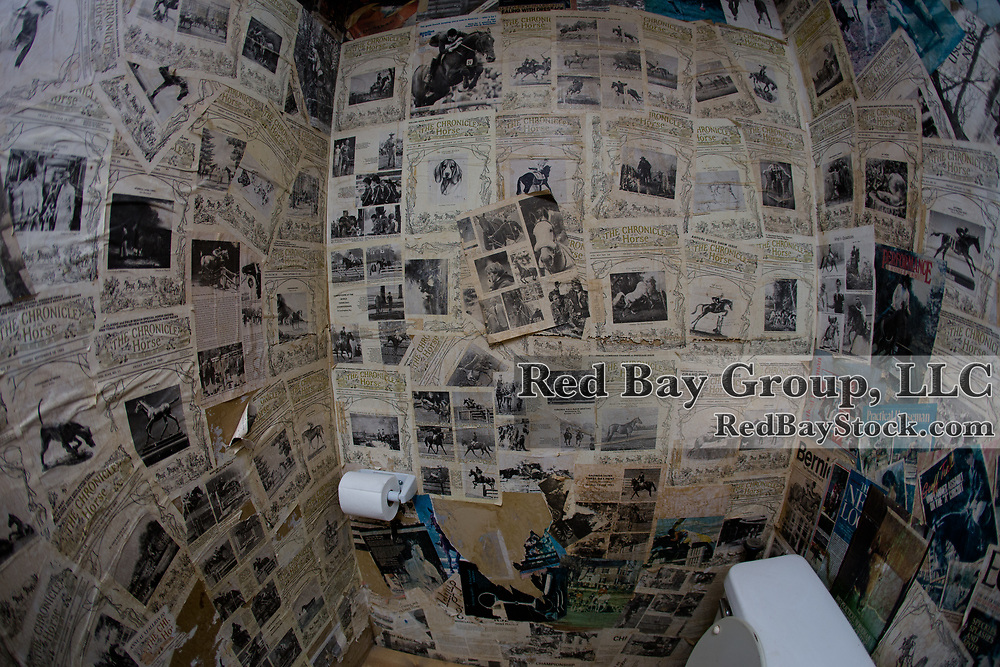 A bathroom wallpapered with old Chronicle of the Horse magazine covers.