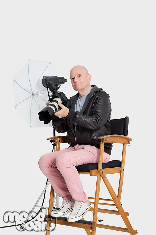 Portrait of senior photographer sitting on director's chair with camera